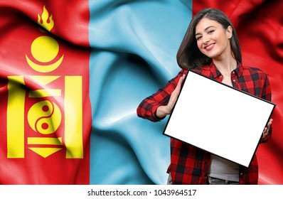 Woman holding blank board against national flag of Mongolia