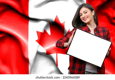 Woman holding blank board against national flag of Canada