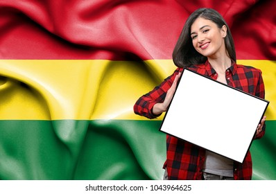 Woman holding blank board against national flag of Bolivia