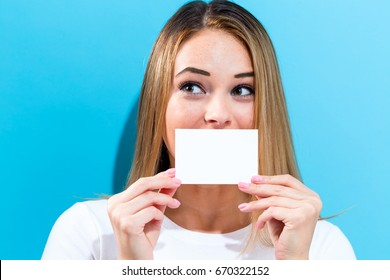 Woman holding a blank message card in front of her face
