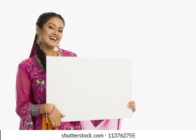Woman holding a blank placard and smiling