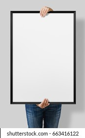 Woman holding a blank poster with black frame mockup isolated on a gray background.