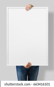 Woman holding a blank poster with white frame mockup isolated on a gray background.