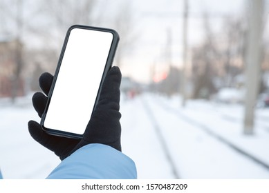 Woman is holding a blank screen mobile phone with copy space for text or for online schedule of tram route and standing on a tramway stop.