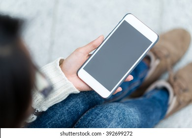 Woman holding the blank screen of mobile phone