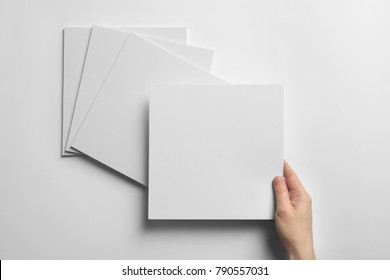 Woman holding blank sheet of paper on white background. Mock up for design