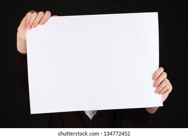 Woman holding blank sign in front her face, isolated on black