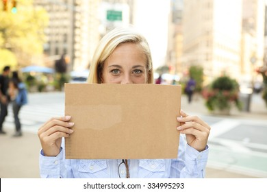 A woman holding up a blank sign in front of her face.