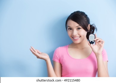 Woman holding a blood glucose meter to prevention diabetes and show something isolated on blue background, asian