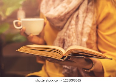 Woman holding book and cup of hot tea drink at cafe