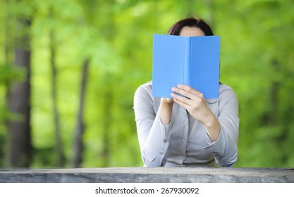 Woman holding book in front of her face