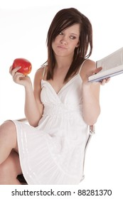A woman holding  a book in her hand looking bored and holding an apple in her other hand.
