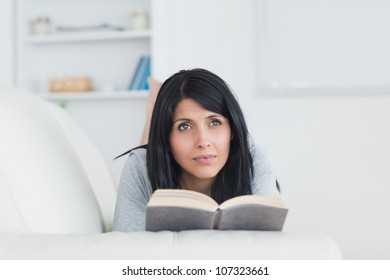 Woman holding a book while laying on a sofa in a living room