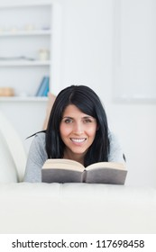 Woman holding a book while smiling and lying on a couch in a living room