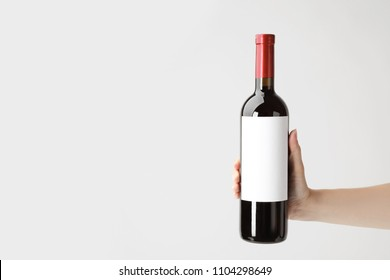 Woman holding bottle with delicious wine on white background
