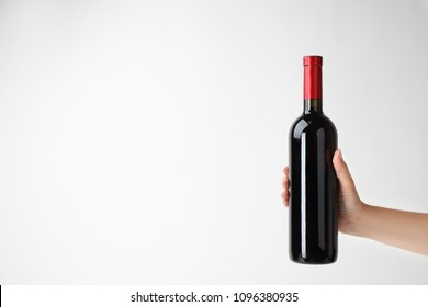Woman holding bottle of expensive red wine on light background