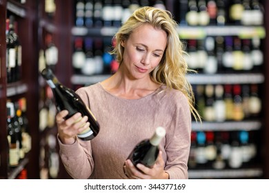 Woman holding bottles of wine in supermarket