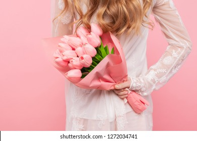 woman holding a bouquet of beautiful pink tulips, on a pink background, Valentine's Day, International Women's Day