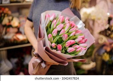 Woman holding a bouquet of pink tulips wrapped in a pink paper on the background of flower shop