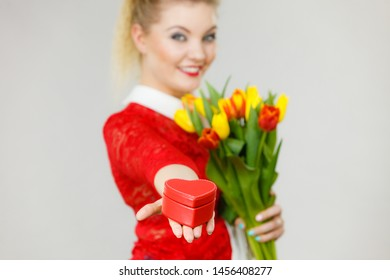 Woman holding bouquet of tulips flower and gift box in heart shape. Womans day, 8 march present.