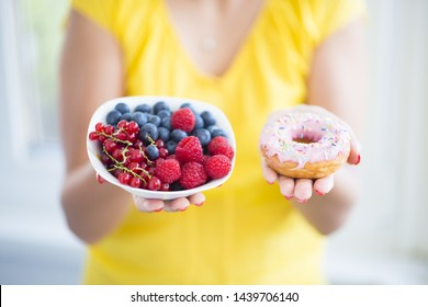 Woman holding bowl with healthy berries and colourful donut, choose healthy eating