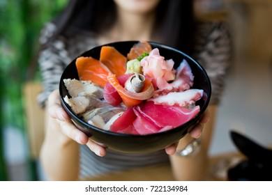woman holding a bowl of sashimi, japanese popular cuisine