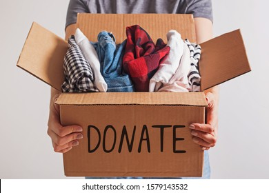 Woman holding a box with clothing close-up. Clothes donation or recycling.