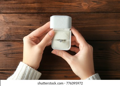 Woman holding box with luxury engagement ring on wooden background, closeup