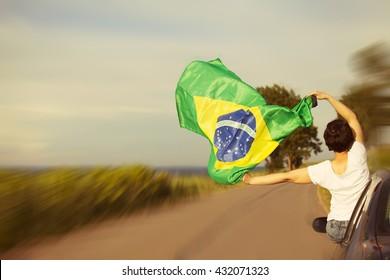 Woman holding Brazil flag - Sport fans traveling to Rio de Janeiro