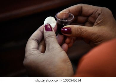 Woman holding bread and wine in a Holy communion.