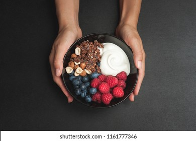 Woman holding breakfast bowl. Healthy breakfast idea with yoghurt, chocolate granola, raspberry, nuts and blueberry