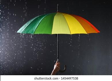 Woman holding bright umbrella under rain on dark background, closeup