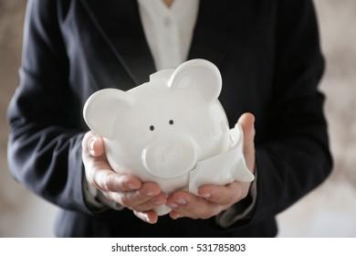 Woman holding broken piggy bank