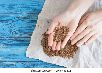 Woman holding brown flax seeds. Top view