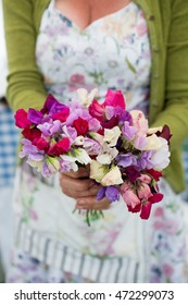 A woman holding a bunch of colourful sweet peas in outstretched hands