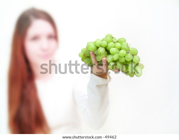 Woman holding a bunch of green grapes into the camera. Grapes and hand in focus.
