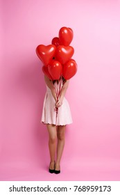 Woman holding bunch of heart shape balloons