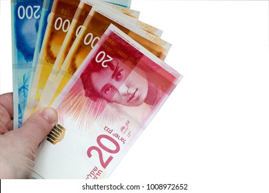 Woman holding a bunch of Israeli New Shekel banknotes in her hands. White background with copy space