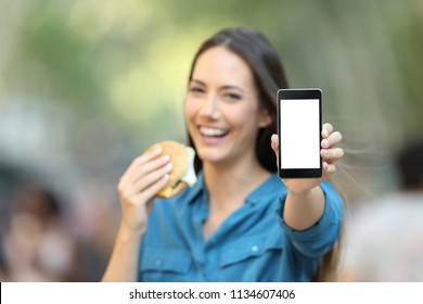 Woman holding a burger showing a blank phone screen mock up on the street