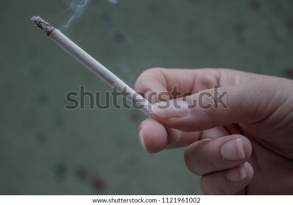 woman holding burning cigarette in hand.harm to health