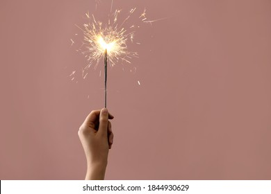 Woman holding burning sparklers on pink background, closeup. Space for text