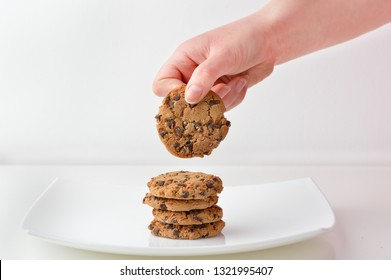 Woman holding by her hand a chocolate cookie from a white pl