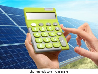 Woman holding calculator and solar panels on background. Reduction of expenses on electricity