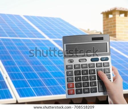 Woman Holding Calculator Solar Panels On Stock Photo (Edit Now