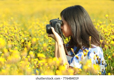 Woman holding camera take photo in yellow flower field