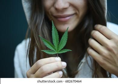 woman holding a cannabis leaf