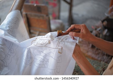 woman holding canting and sketching batik in white fabric,as process of batik painting