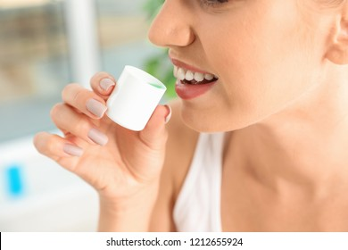Woman holding cap with mouthwash, closeup view. Teeth care