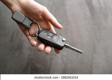 Woman holding car flip key on grey background, closeup