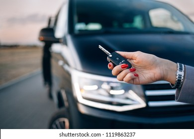 Woman is holding car key in the front of van